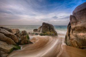 water rushes to the ocean between rocks in cabo san lucas mexico