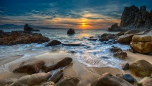waves rush past rocks during sunrise landscape photography
