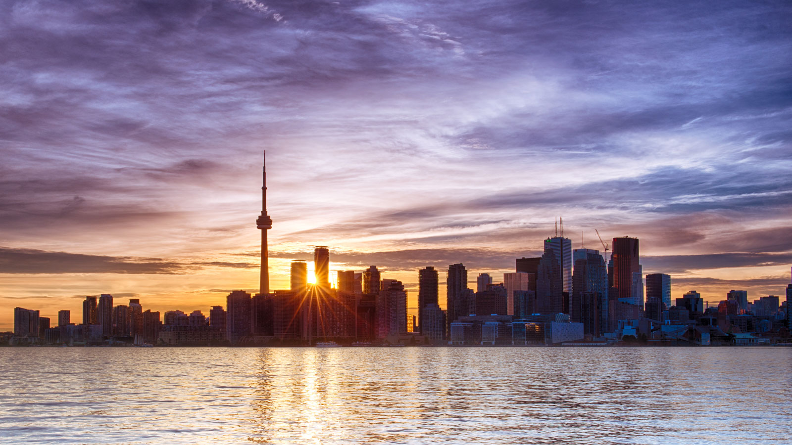 The sun sets behind the distinctive skyline of Toronto cityscape landscape photography