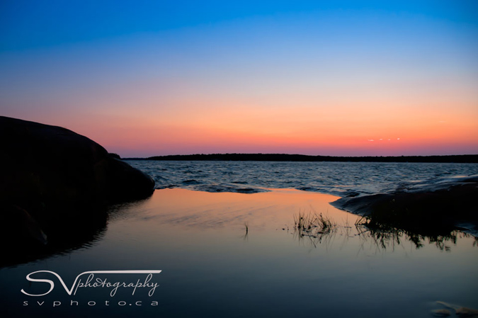 """Juxtaposition of the calm waters of the """"catch basin"""" on the rocks at Harold's Point and the rough water's beyond"""