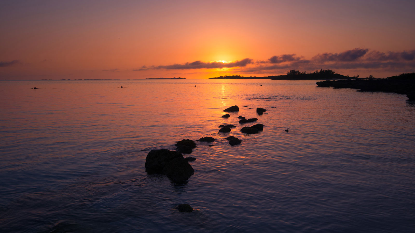 Rocks dot the water leading the say to the sunrise on Paradise Island Bahamas