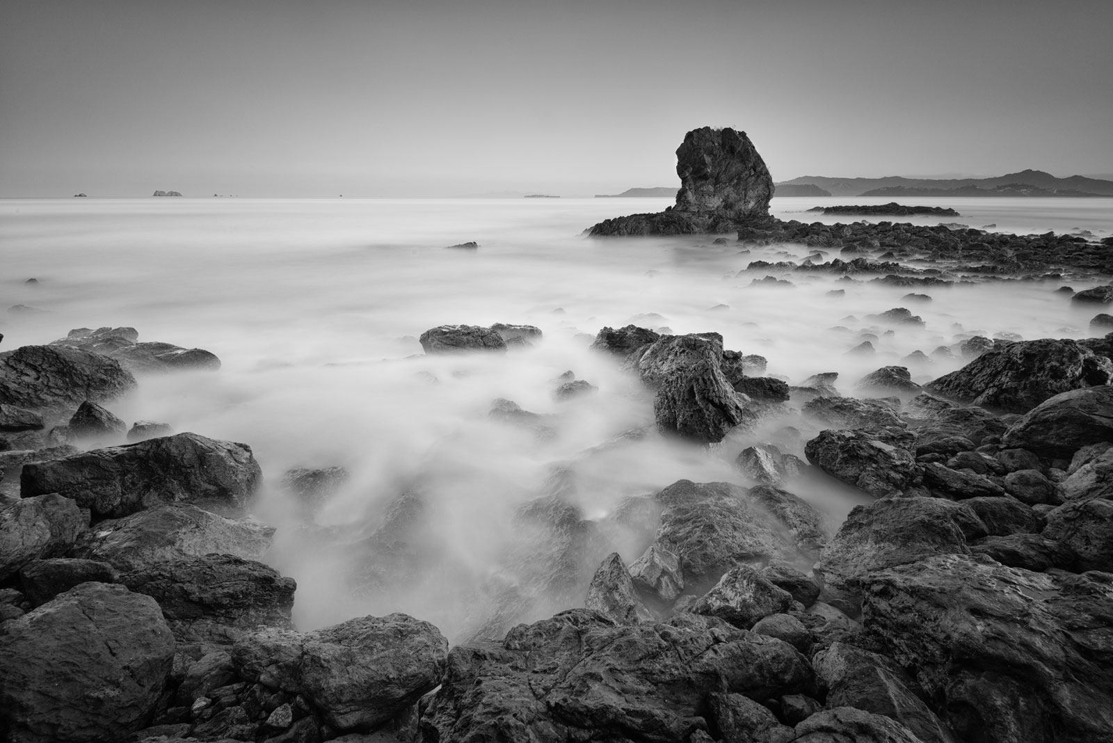 long exposure black and white rocks in ocean playa conchal